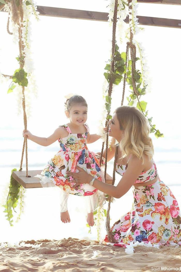 Plage photo mère fille robes de meme tissu et meme motif fleurie mais différents modèles, idée tenue mère-fille, vetement mere fille qui se ressemblent