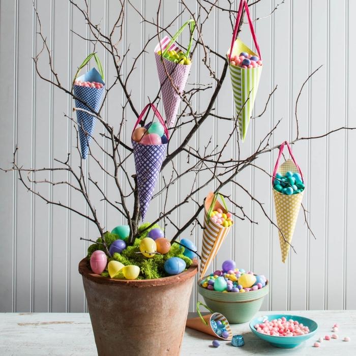 inspiration activité de paques pour enfants, comment faire un cône en papier DIY, suspendre des oeufs aux branches séchées