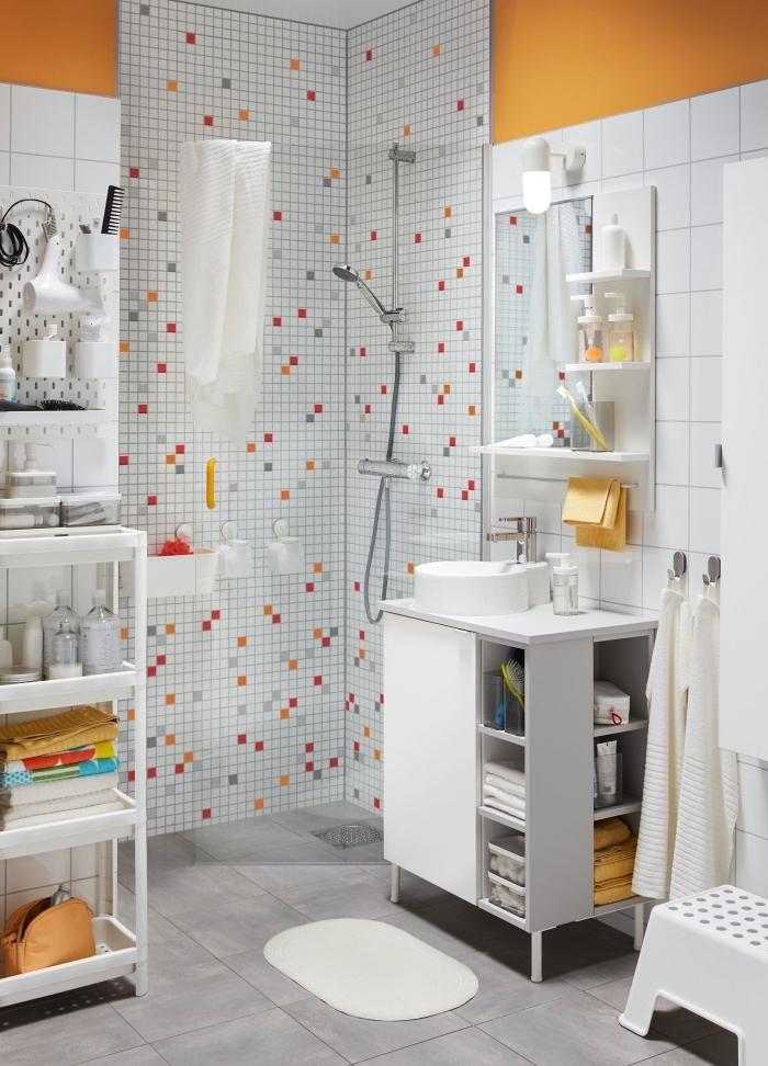 decoration petite salle de bain en blanc et gris avec accents orange, idée rangement ouvert pour affaires de bain