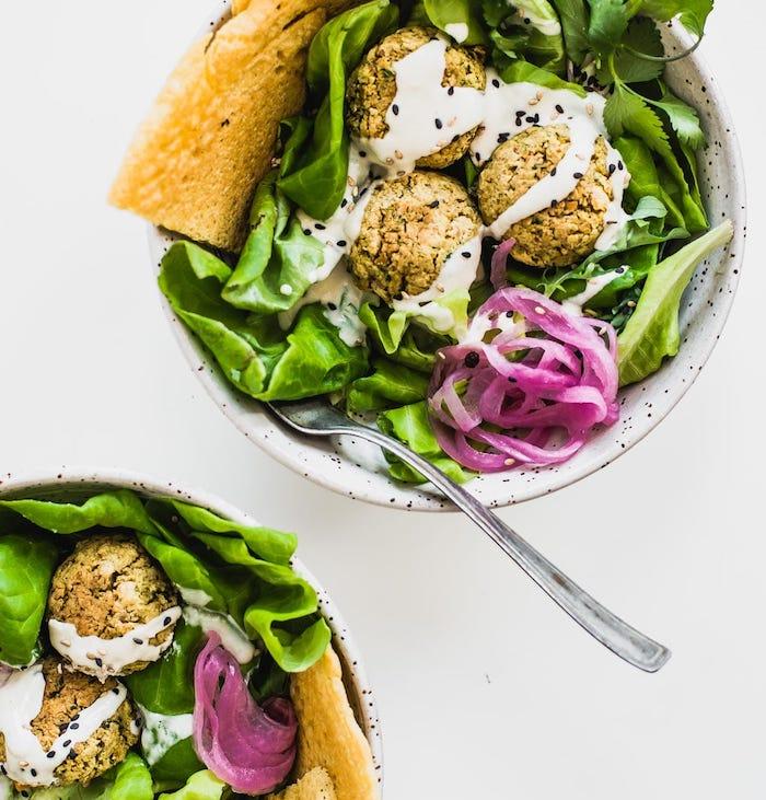 idée repas simple de tous les jours, boules de pis ciche, falafel à la sauce tahini sur salades vertes avec tranches de pain