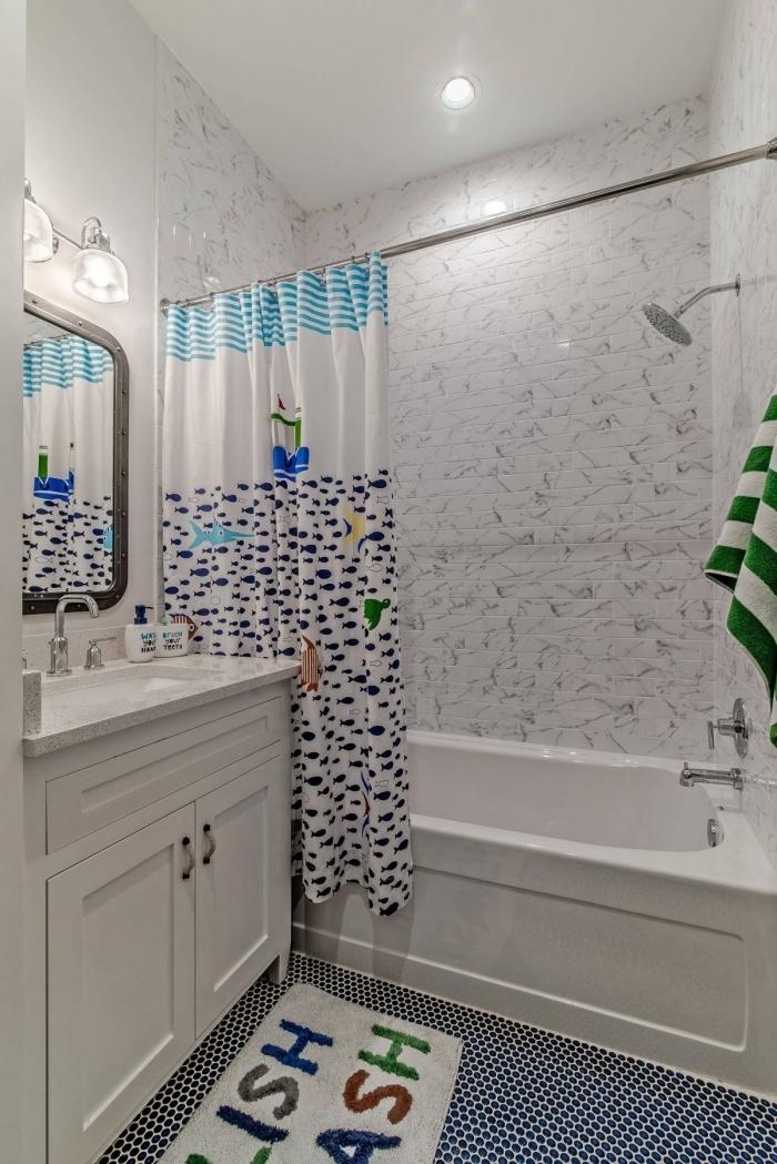 agencement salle de bain petit espace avec baignoire enfant et rideaux de douche aux motifs marines en blanc et bleu