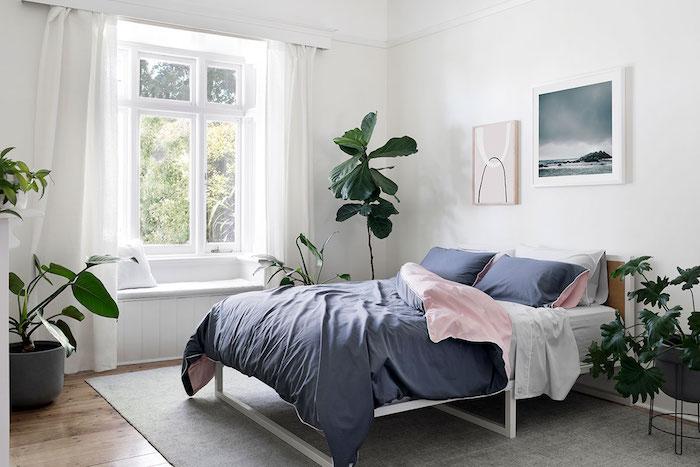 Chambre à coucher blanche décodé de plantes vertes intérieur, lit double avec linge rose et bleu, chambre boheme chic déco mignonne