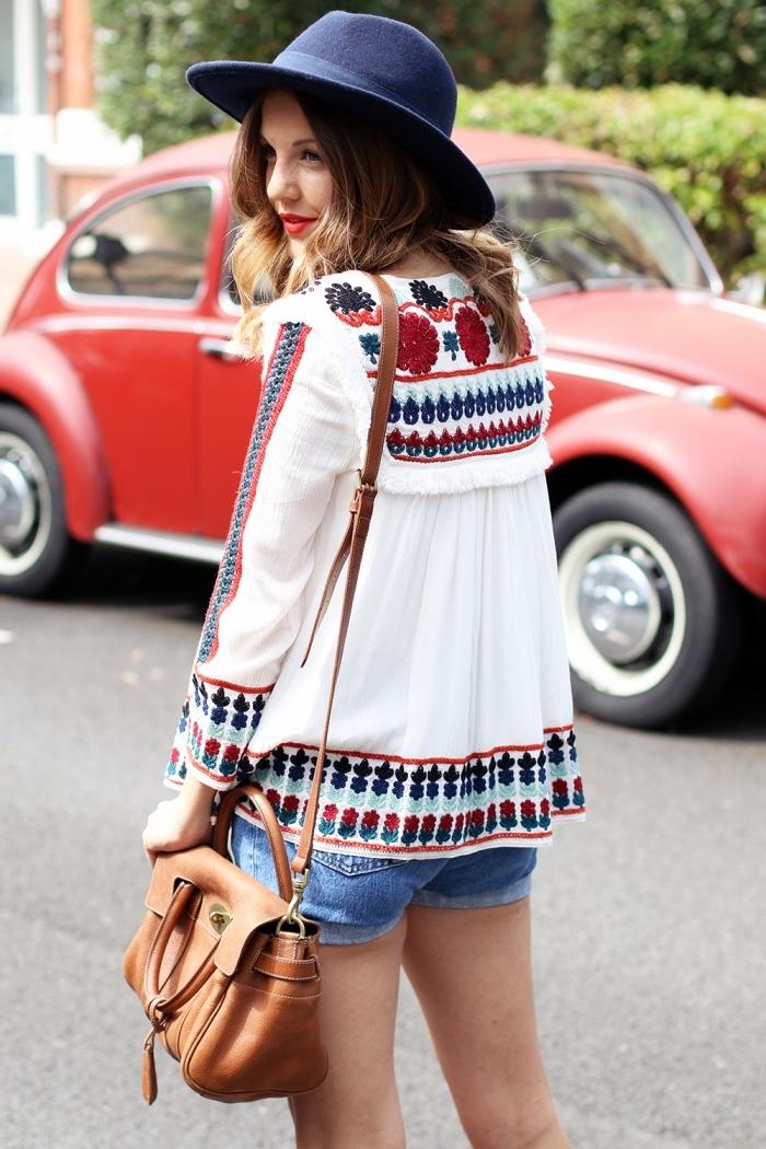 exemple de tenue hippie chic été en shorts denim et blouse à motifs folkloriques avec capeline et sac à main