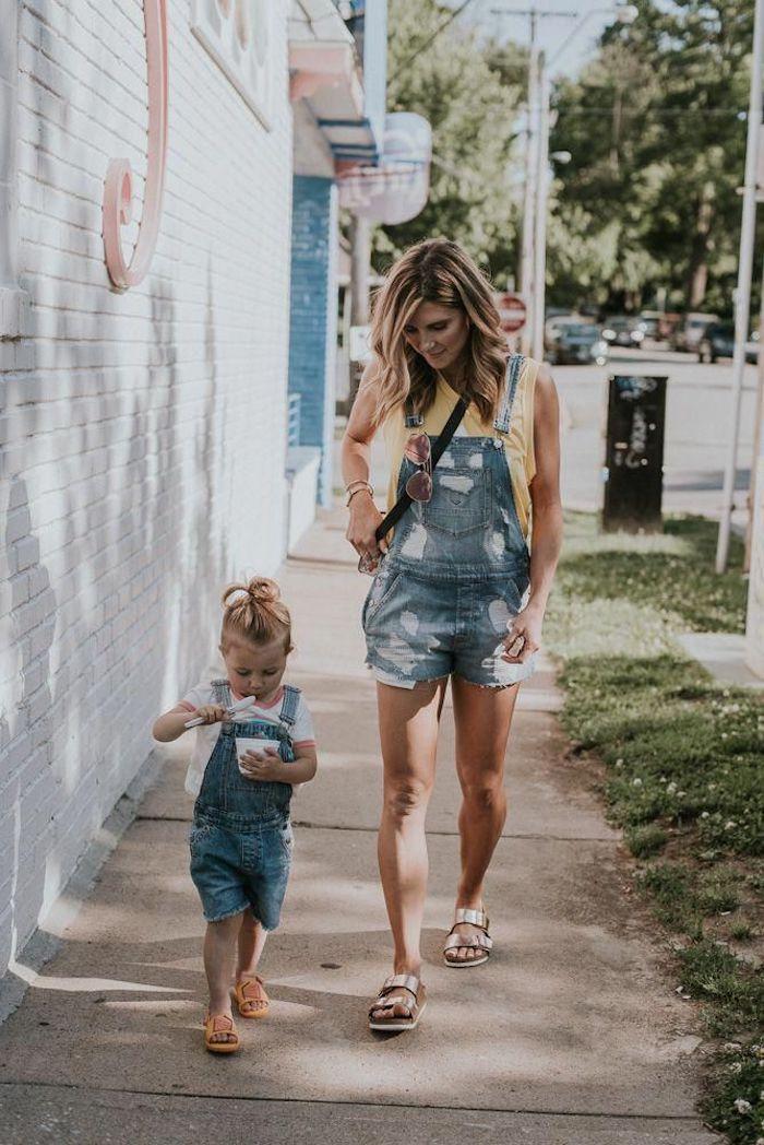 Adorable enfant avec son yaourt glacé habillée de la même façon que sa mère en salopette jean short et t-shirt