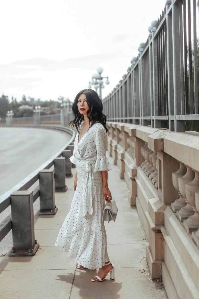 idée de tenue blanche femme élégante en robe longue à volants et décolleté en V assortie avec sandales et sac à main