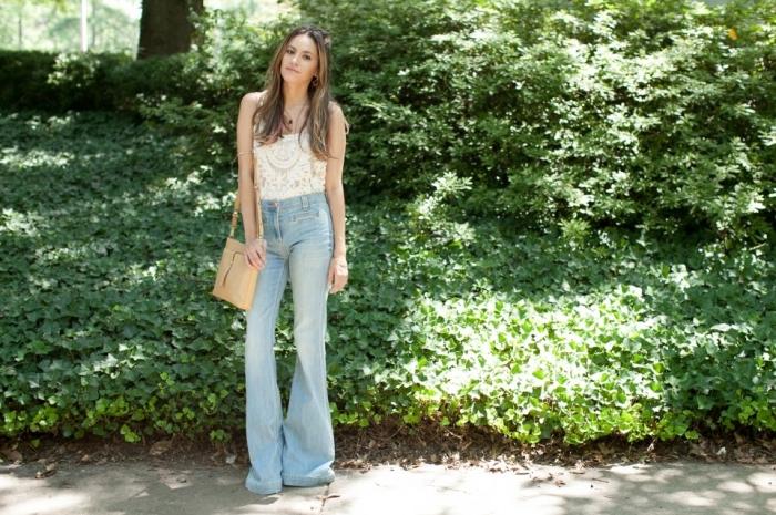 idée de tenue rétro style en jeans évasés à taille haute combinés avec top blanc en dentelle mandala et sac bandoulière beige