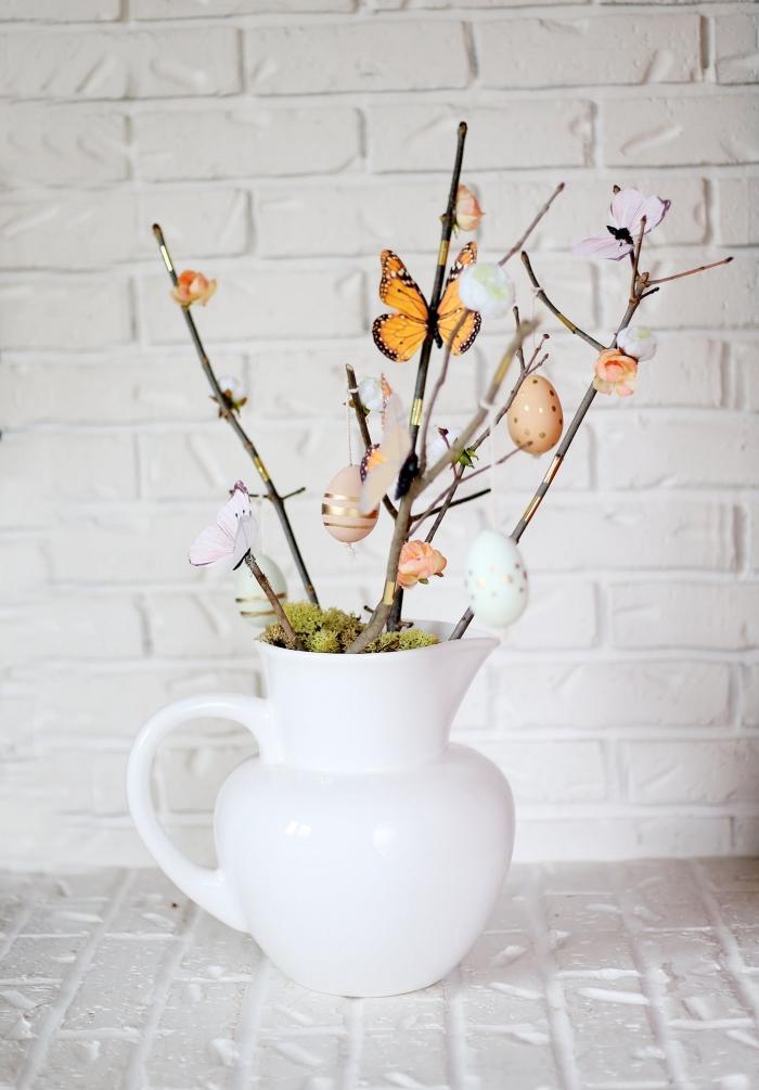 décoration de paques à fabriquer avec branches et oeufs décorés, vase blanc rempli de branches décorés de figurines pâques