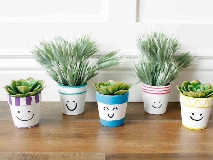 de simples bonhommes en terre cuite dessinés au feutre et peinture acrylique, décoration pot de fleur mignonne