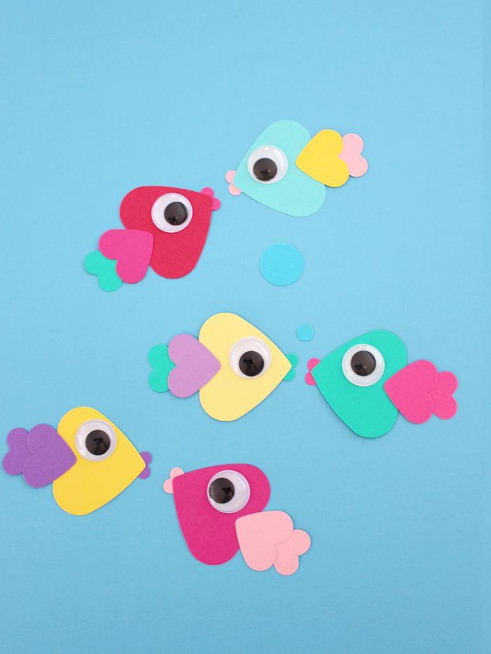 idée d activité manuelle été originale avec des coeurs de papier collés ensemble pour constituer des poissons avec des yeux mobiles sur fond bleu