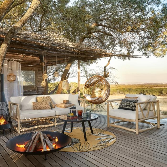 Belle vue d'une terrasse bien aménagée, canapé bois et coussins blanches, diy cheminée tapis ronde jaune, balançoire oeuf chaise
