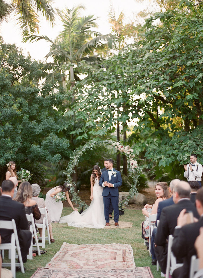 Arc fleurie avec branches feuilles vertes, mariage location exotique, bohème chic tapis oriental, femme robe longue sirène