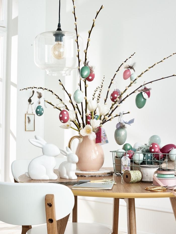 idée activité paques facile, bouquet de branches décorés d'oeufs dans un vase rose pastel, modèle centre table diy pour Pâques