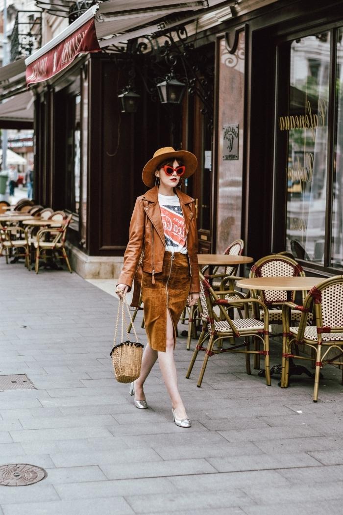 modèle de veste simili cuir en marron combinée avec jupe en velours fendue et t-shirt blanc, accessoires capeline et sac à main de style boho chic