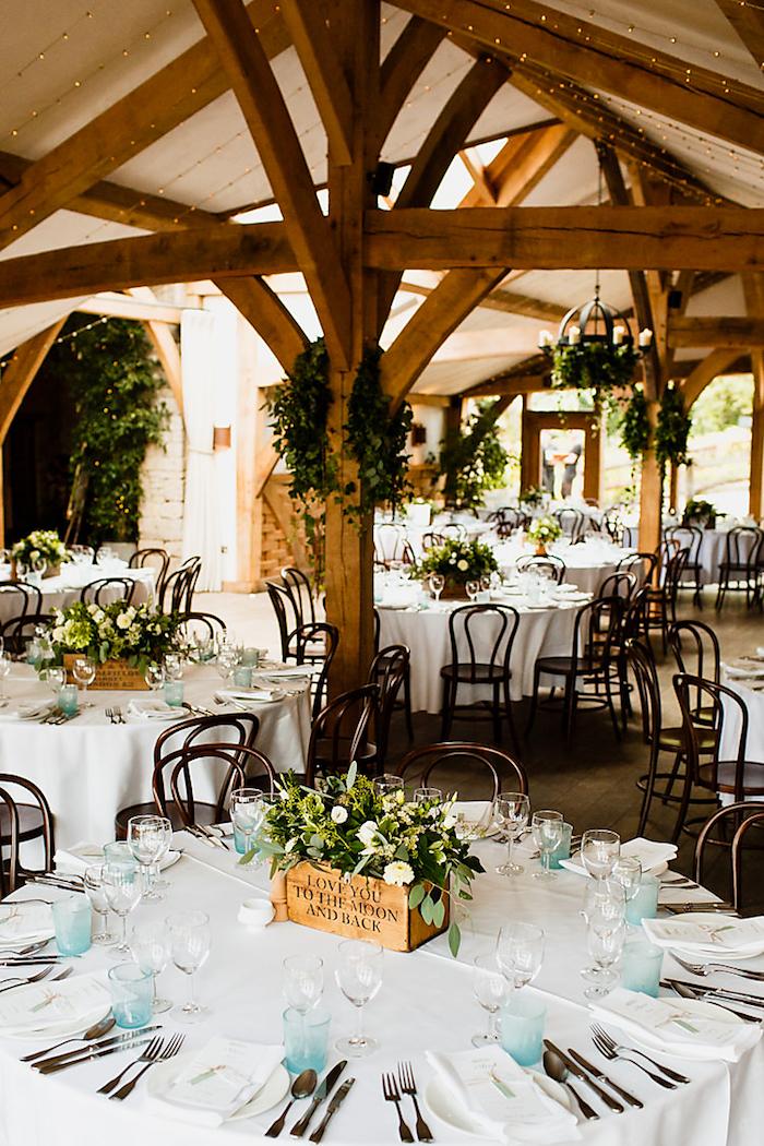 Table ronde rangé simplement de fleurs blanches, verres bleu claires, idée deco mariage champetre, style boheme chic mariage plein nature