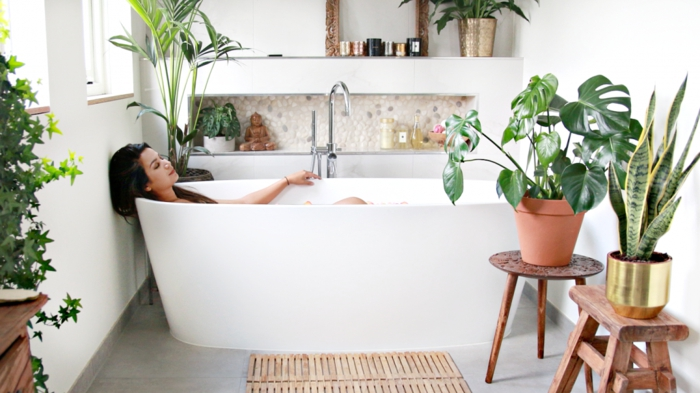 Baignoire ovale dans une salle de bain peinte en blanc avec beaucoup de plantes vertes, quelle couleur pour une salle de bain, déco petite salle de bain