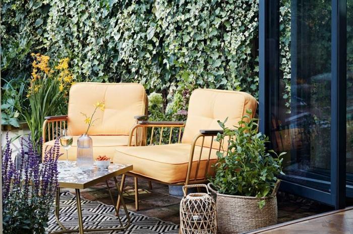 Fauteuils jaunes deco terrasse, aménagement terrasse de jardin option extérieur fleurs violets et oranges, tapis géométrique noir et blanc
