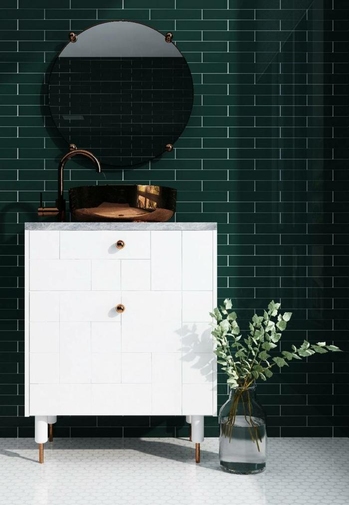 Carrelage vert sombre, vase en verre sur le sol, meuble lavabo avec placards, lavabo cuivre, miroir ronde sur mur verte, quelle couleur pour une salle de bain idée originale