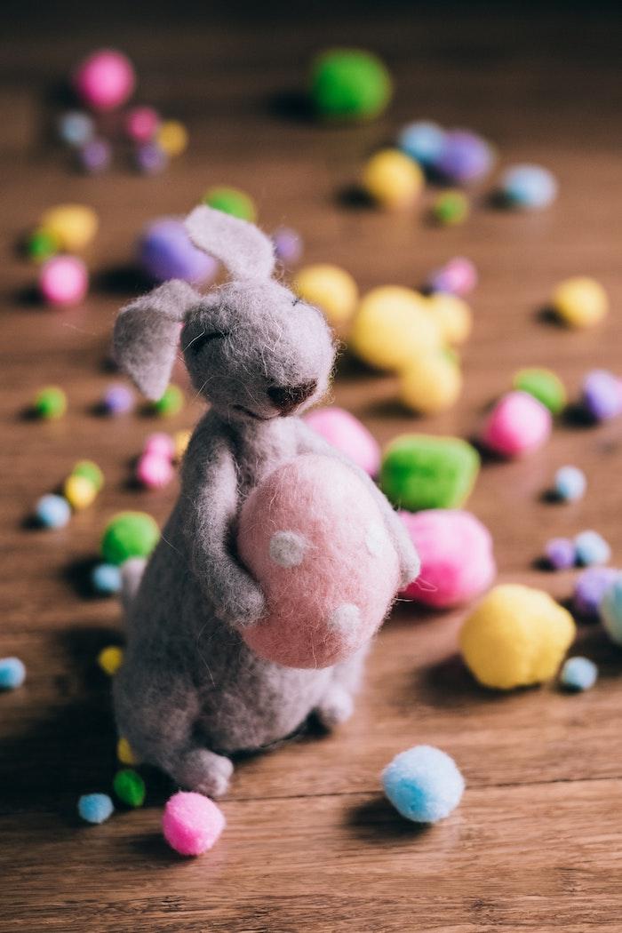Lapin décoratif avec oeuf de paques coloré dans les mains, idée quelles sont les meilleurs cadeaux de Pâques pour un proche ou un ami