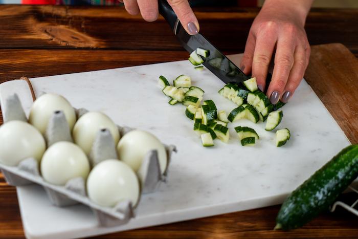 couper une concombre en dés pour faire entree de pques, recette oeuf mimosa simple et rapide