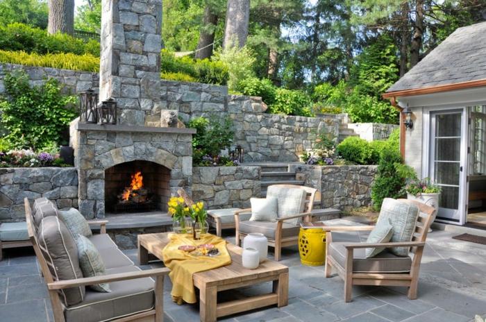 Cheminée en pierres extérieur, idée jardin paysager, amenagement terrasse jardin jolies fleurs table basse bois et canapé meubles jardin
