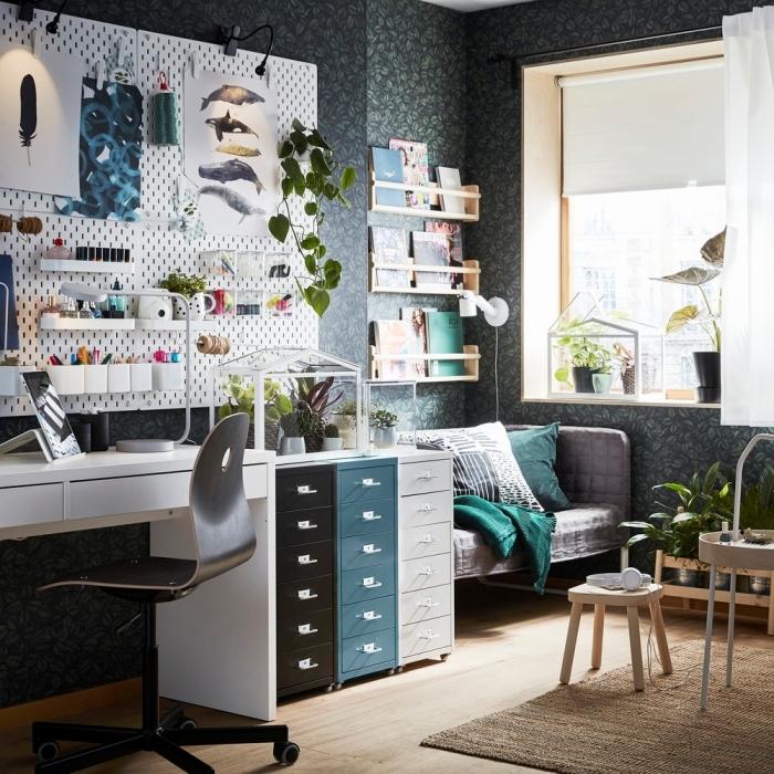 aménagement console bureau blanc dans un salon aux murs foncés habillés en papier peint motifs tropicaux en noir et vert