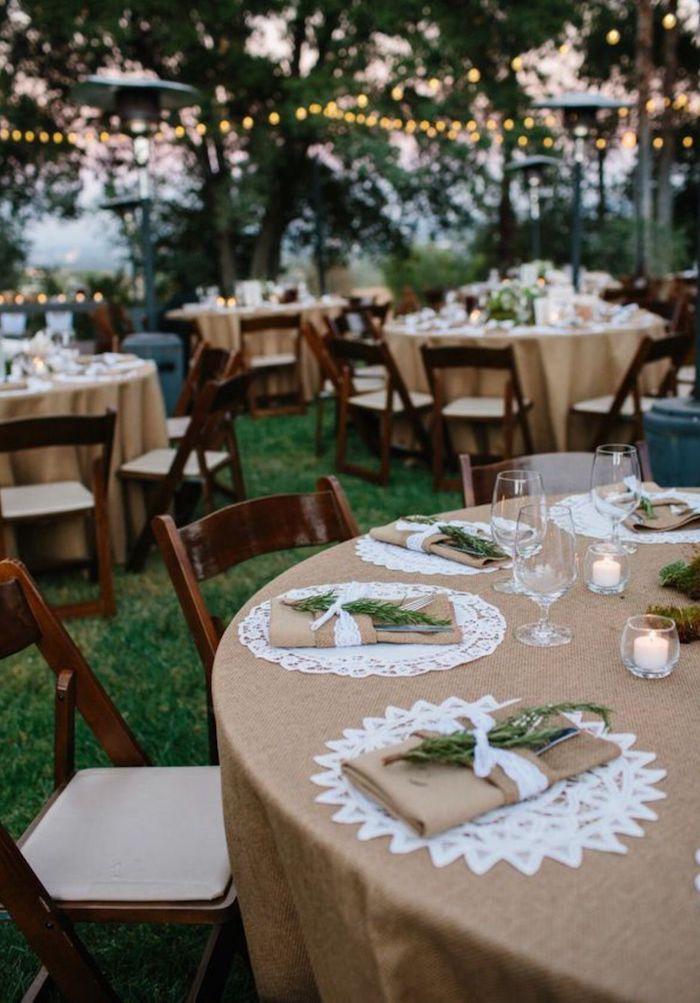 Table ronde avec nappe en lin et branches vertes sur les serviettes, guirlandes lumineuses decoration mariage champetre, décoration mariage champêtre