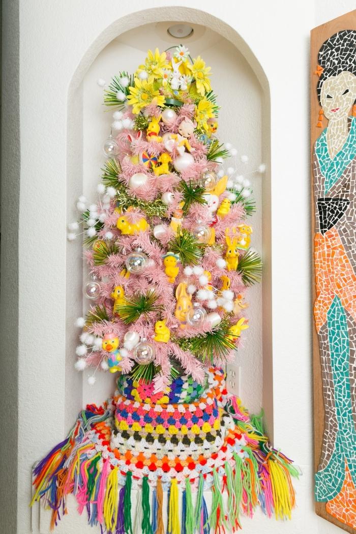 exemple comment faire une jolie deco de paques murale avec faux sapin décoré de guirlandes roses et figurines pâques