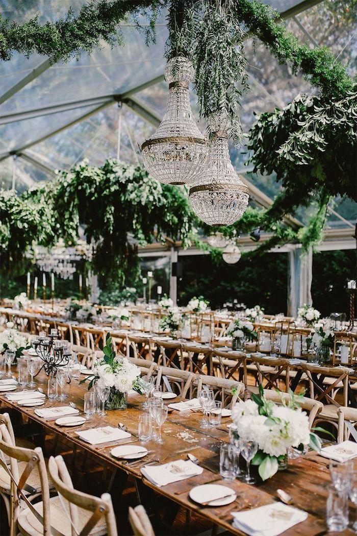 Table longue en bois, lustre baroque avec cristaux, déco plantes vertes toit verre, centre de table mariage champetre reception originale
