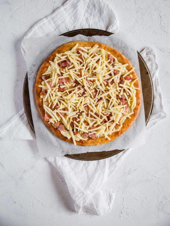 fromage râpé et bacon pour faire une pizza sans gluten sur pâte à pizza sans gluten dans plaque de cuisson