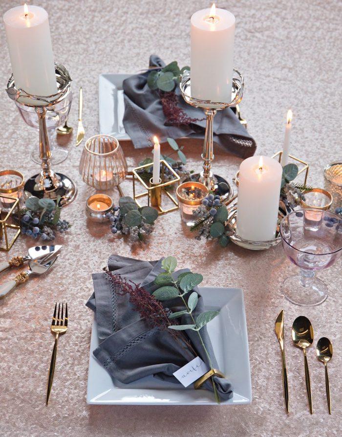 Simple assiette joliment décoré avec plante verte, nappe en lin bleu sombre, bougies et branches mariage champêtre chic, décoration élégant au style rustique