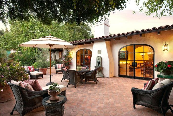 Maison basse à un étage amenagement exterieur jardin, idee amenagement jardin simple table ronde avec canapés et chaises de repos