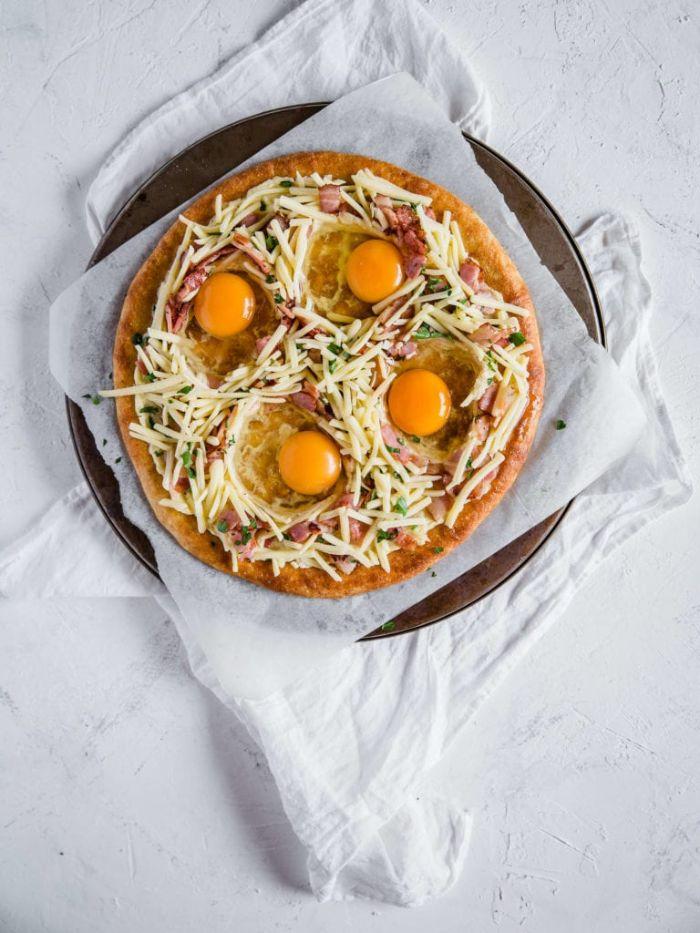 pizza sans gluten avec fromage, bacon et des oeufs cassés sur pâte à pizza sans gluten aux fromages, petit dejeuner ideal pizza maison
