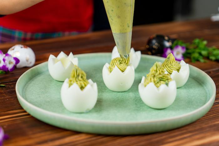 verser la farce pour oeufs mimosa à l'aide de poche à douille, recette entree de paques originale, blancs d oeufs farcies mélange jaunes d oeufs, avocat, ail, moutarde