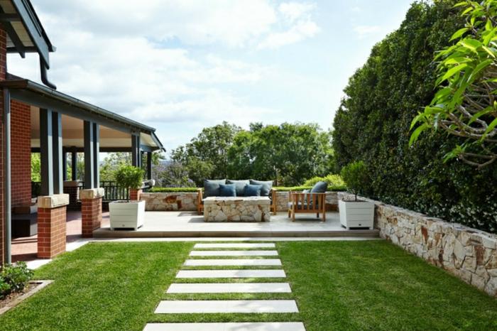 Canapé coussins et table en pierres, aménager une terrasse, jardin paysager, amenagement exterieur jardin