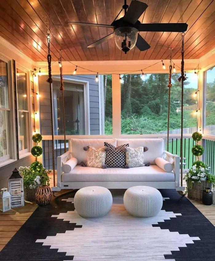 Canapé blanche et guirlande lumineuse, tapis blanc et noir idee jardin paysagiste, terrasse exterieur au jardin original