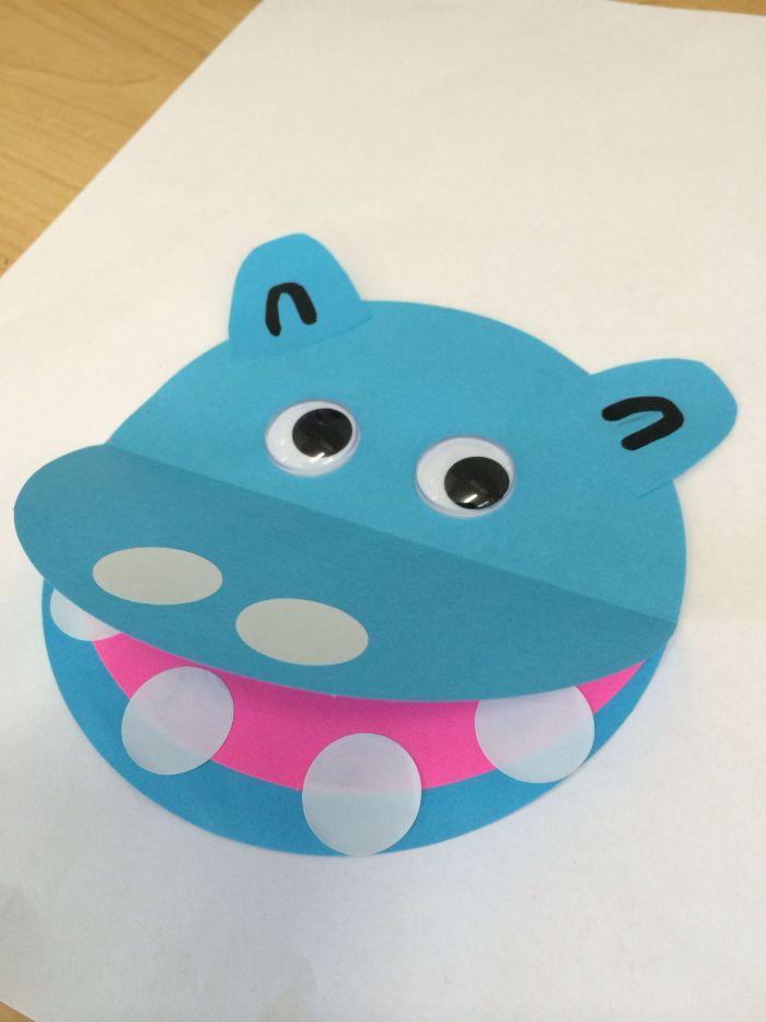 hippopotame en papier bleu sur un bout de papier blanc avec de syeux mobiles et dentes de papier blanc, activité créative en papier pour tout petit