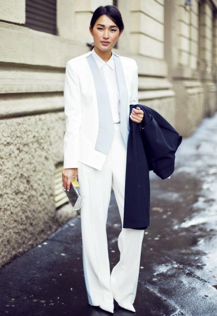 Jolie femme en smoking blanc avec manteau noir a la main, ensemble costume femme, tailleur blanc pour femme avoir de la swag