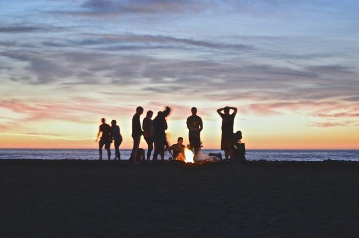 Soirée autour le feu à la plage, photo amis amusement au coucher de soleil au bord de la mer, organisation enterrement de vie de garçon