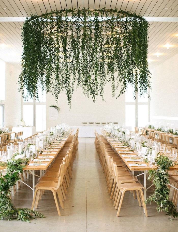 Grand lustre décoré de guirlande verte avec feuilles d'arbre décoration mariage champêtre chic, menu mariage champetre