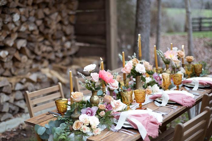 Table en bois décoré de fleurs, bougies dorés et assiettes en or, deco table mariage champetre, centre de table mariage champetre