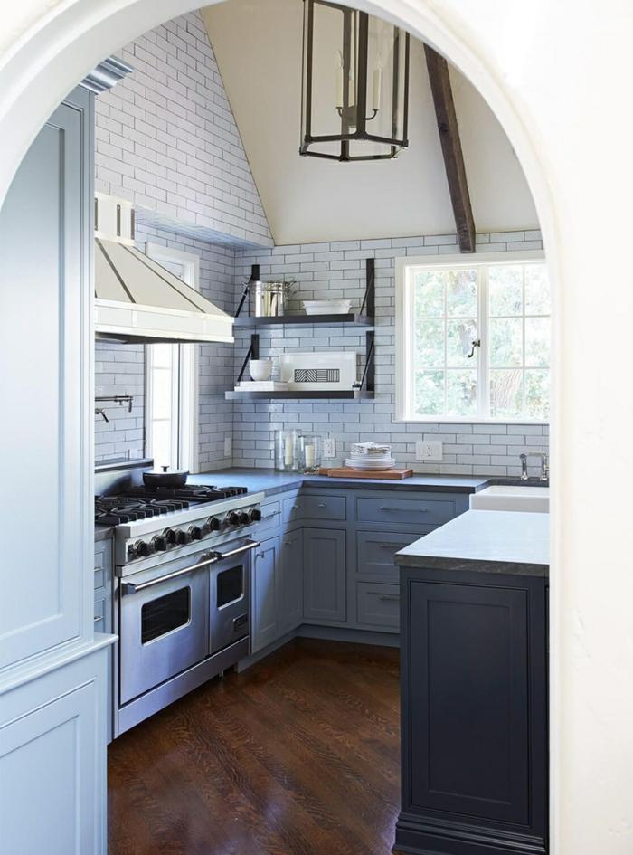 Vue de la cuisine de l'entrance en arche, idee cuisine moderne blanche, comment aménager la cuisine claire avec ilot sombre en bleu