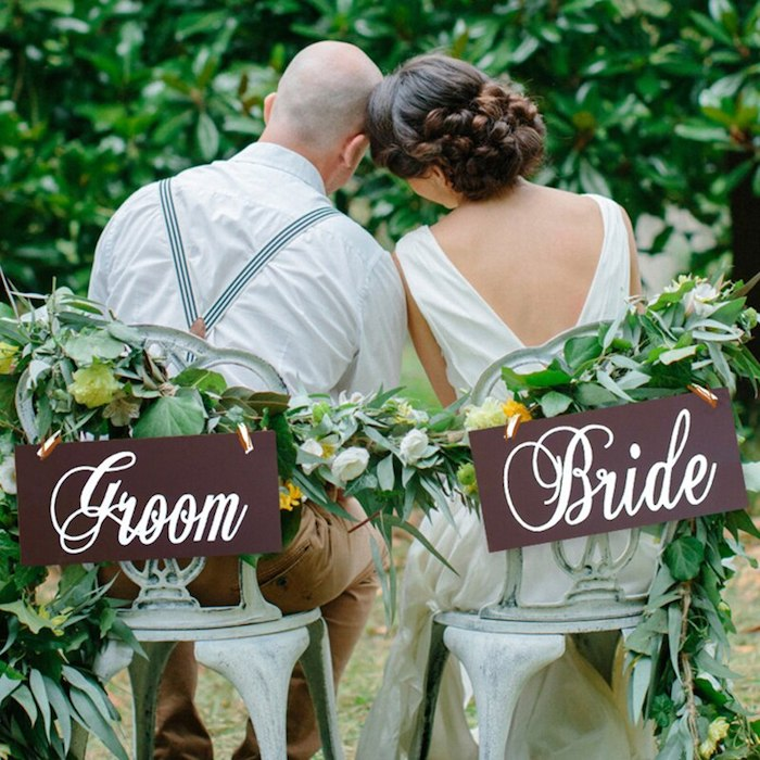 Couple marié assieses sur chaises centre de table mariage champetre reception à l exterieur femme en robe blanche longue