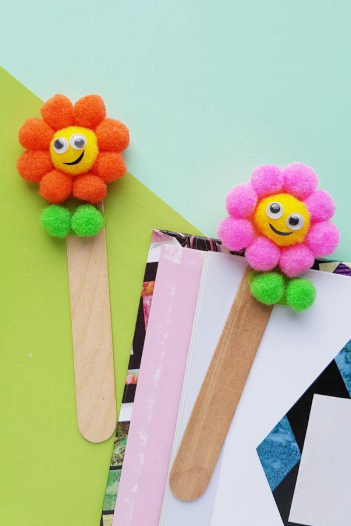 marque page diy en batonnet de glace et pompons colorés rangés pour figurer un motif fleur, activite enfant 5 ans