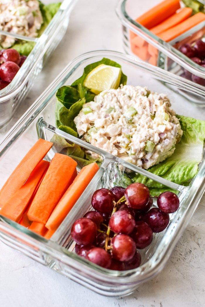 idée repas midi, salade au thon, mayonnaise dans une feuille de laitue, raisins et baguettes de carotte
