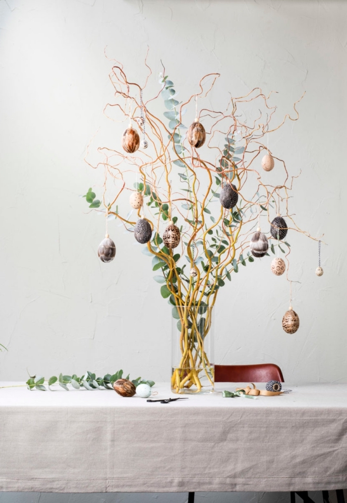 exemple de deco paques moderne et fait maison, diy bouquet de branches colorées en cuivre et or avec décoration oeufs suspendus