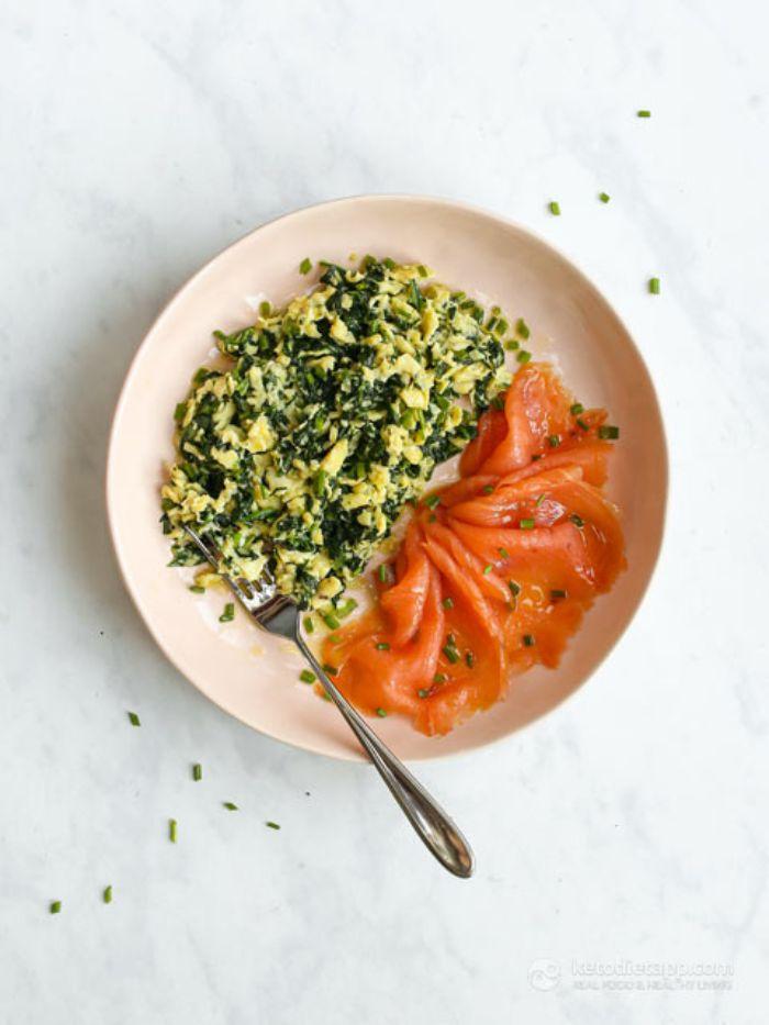 oeufs brouillés aux epinards avec des tranches de saumon fumé dans assiette blanche, recette cetogene de petit dejeuner
