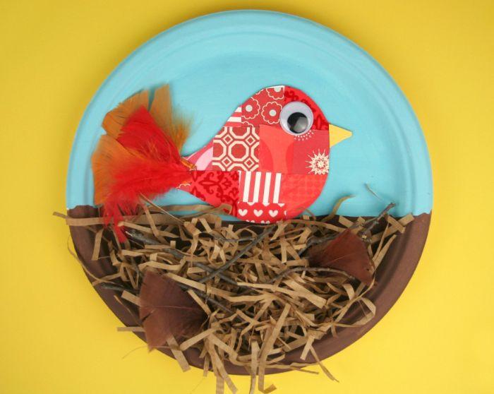 poussind e papier rouge et plumes rouges perché sur un nids en ficelles de papier et plumes fabriqué dans assiette de papier, activité manuelle facile en papier