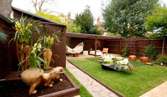 Petit coin avec pelouse verte, table basse en verre et bois flotté, aménager une terrasse, idée decoration jardin terrasse