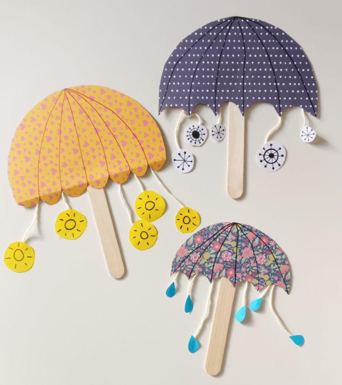 idee de bricolage de printemps original, petit parapluie en papier et batonnet de glace avec gouttes de papier