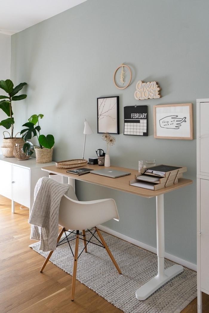 espace de travail dans une pièce aux murs vert menthe avec parquet bois, modèle de bureau blanc et bois pour home office